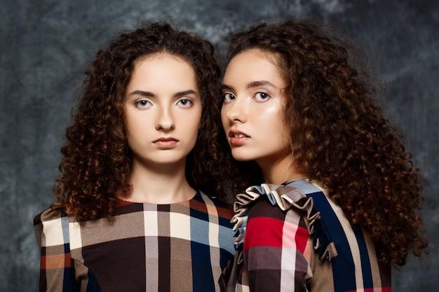 Soeurs jumelles posant sur gris