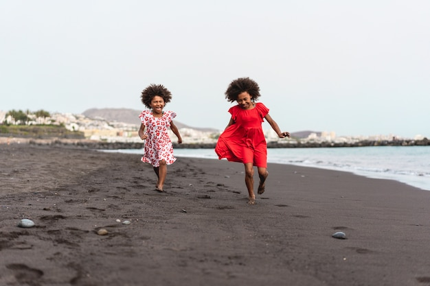 Sœurs jumelles qui courent ensemble sur la plage