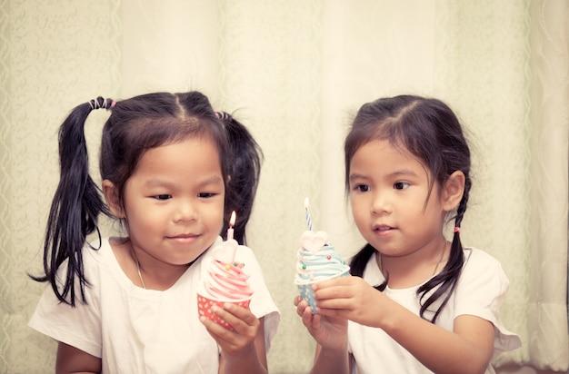 Sœurs s'amusant ensemble soufflant anniversaire cupcake, ton vintage couleur