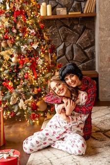 Sœurs s'amusant et s'embrassant près d'un sapin de noël rouge décoré. ils sourient et célèbrent le nouvel an et noël.