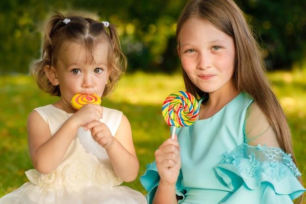 Sœurs avec des sucettes sucrées dans la nature en été dans le parc