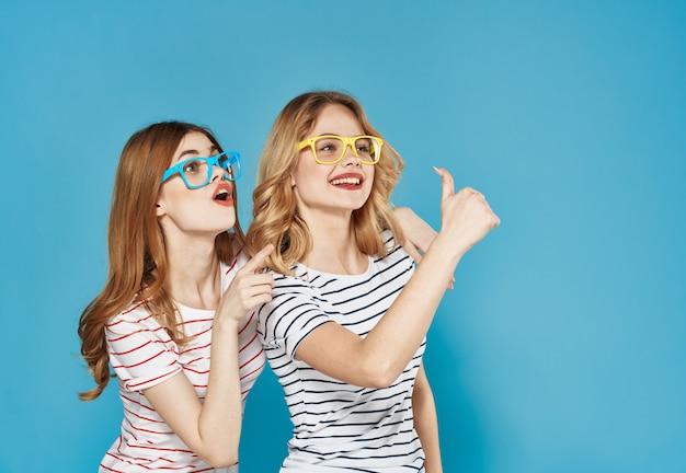 Sœurs suspendues dans des verres multicolores à rayures t-shirts gestes émotions doigts recadrée avec copie