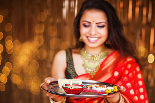 Soft focus portrait d'une femme indienne en sari rouge priant à la célébration de diwali