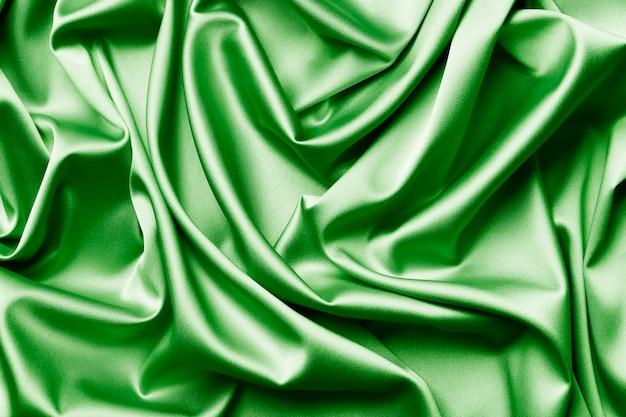 La soie verte élégante et lisse ou la texture satinée peuvent être utilisées comme arrière-plan abstrait. design de fond luxueux