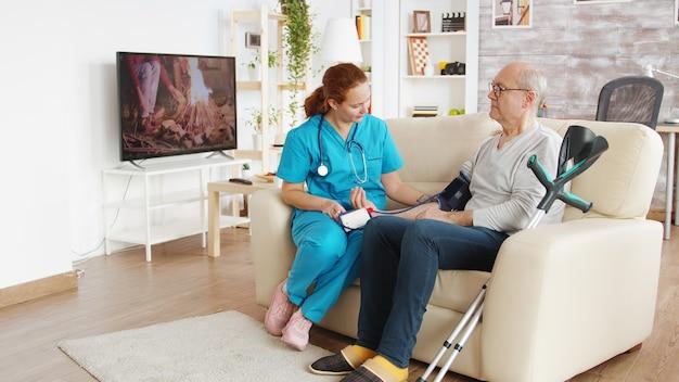 Soignant dans une maison de retraite vérifiant la tension artérielle d'un vieil homme à la retraite. tir révélateur.