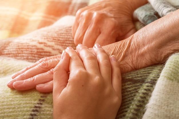 Soignant, main de soignant tenant la main d'un aîné