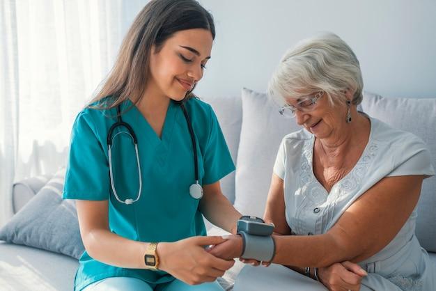 Un soignant mesure la pression artérielle d'une femme âgée à la maison.
