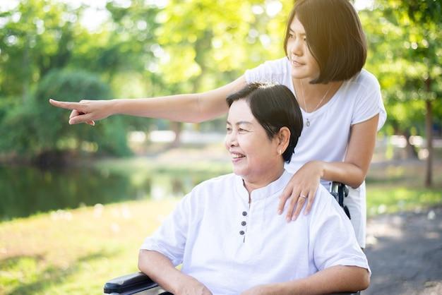 Le soignant prend soin d'une femme asiatique âgée assise sur un fauteuil roulant dans la nature, concept d'assurance soins aux personnes âgées