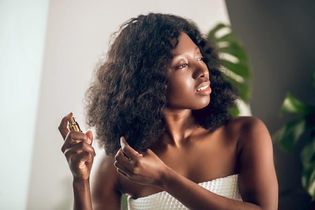 Soin des cheveux. attrayant femme afro-américaine de pulvérisation de sérum sur ses cheveux