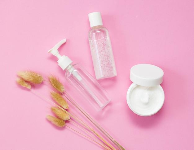 Soin, cosmétique bio pour le visage. bouteilles blanches et transparentes crème sur fond rose