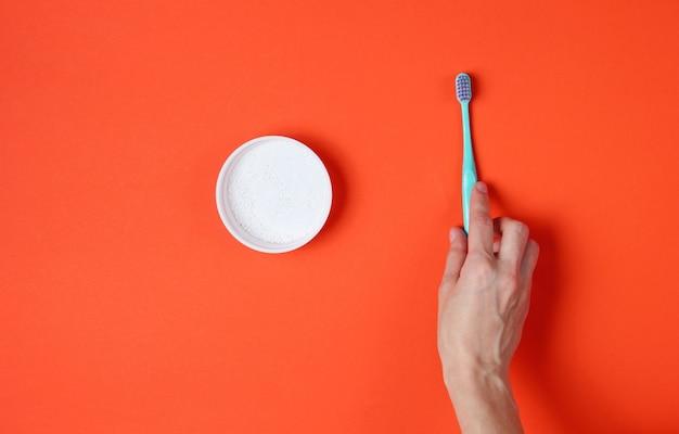 Soin des dents. mains féminines tenant une brosse à dents et poudre à dents sur orange. vue de dessus