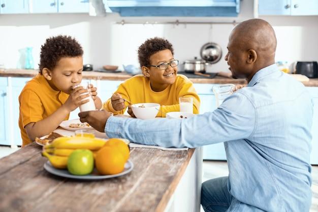 Soin doux. charmant jeune père donnant à son fils un verre de lait et l'aidant à boire pendant qu'ils sont tous assis ensemble à la table et mangeant le petit déjeuner