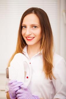 Soin du corps. femme médecin affichant une machine pour l'épilation au laser