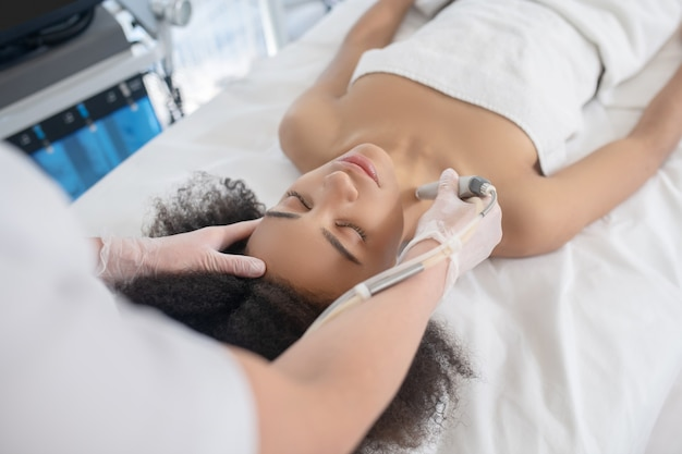 Soin du corps. mains d'esthéticienne dans des gants avec un appareil près du cou de la jeune femme allongée sur un canapé blanc