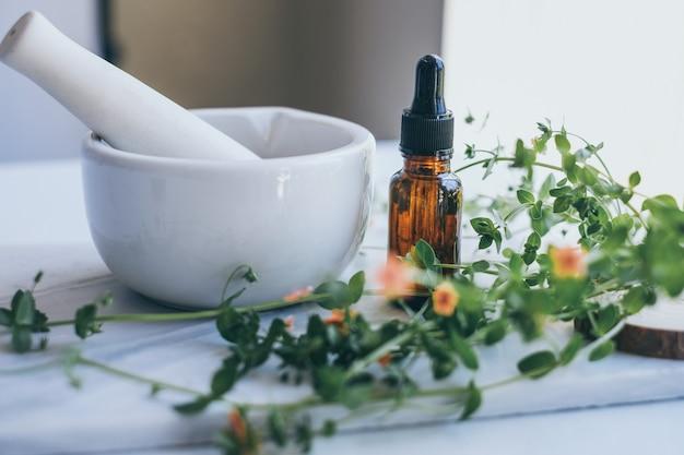 Soin naturel sur table en marbre avec fleurs, feuilles et mortier pilon.