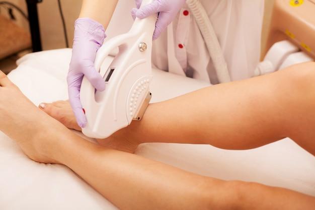 Soin de la peau. épilation sur les jambes, procédure au laser à la clinique.