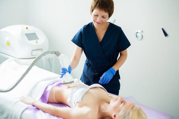 Soin de la peau. une femme est en cours de traitement à la clinique de lipomassage.