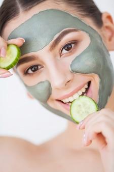 Soin de la peau. jeune femme, à, masque cosmétique argile, tenue, concombre, à, elle, salle de bains
