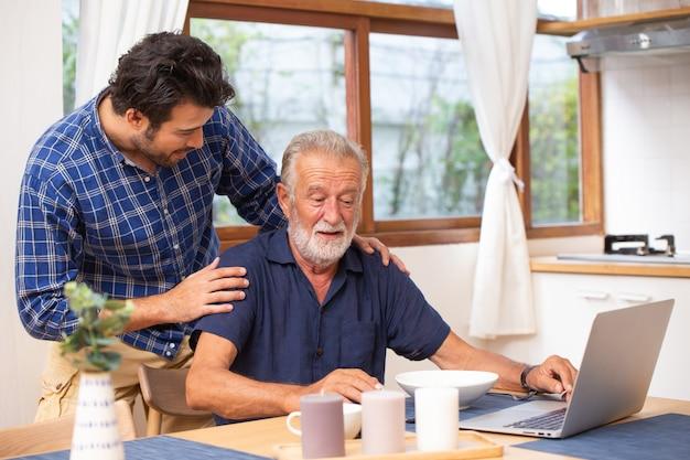 Soins aux personnes âgées à domicile, bon mentor en bonne santé, vieil homme intelligent utilisant un ordinateur portable chez un jeune homme.
