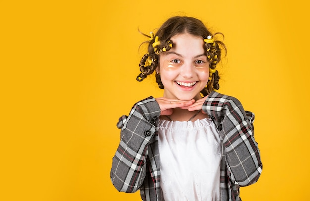Soins capillaires pour enfant. petite femme toilettage avec rouleau à cheveux. patch de thérapie oculaire. beauté et mode. petite fille a des papillotes de cheveux. salon de coiffure pour enfants. coiffure longue saine. créer des boucles d'épingles.
