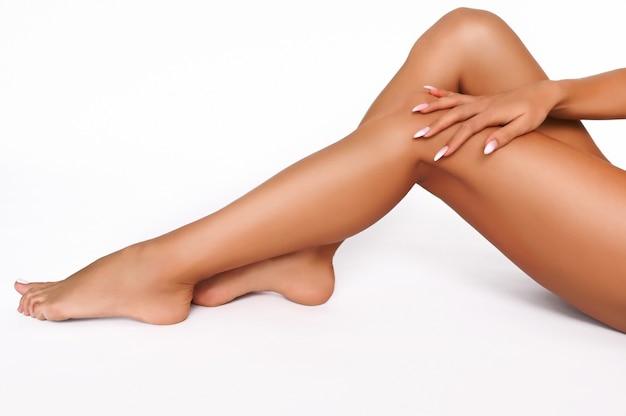 Soins du corps de la femme. gros plan de longues jambes bronzées féminines avec une peau douce et lisse parfaite, pédicure, ongles sains sur fond blanc. concept d'épilation, d'épilation, de beauté et de santé