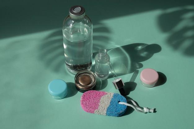 Soins du corps et spa. produits de beauté naturels. crème écologique, sérum, bouteille vide pour les soins de la peau. pipette en verre. pierre ponce pour les pieds. vue de dessus.