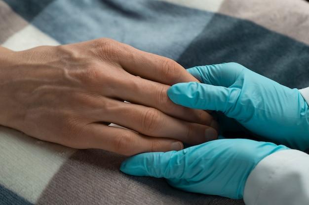 Soins du médecin pour le patient. mains d'une vieille femme dans les bras d'une infirmière. service et soutien aux personnes âgées.
