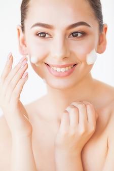 Soins du visage de beauté. femme avec de la crème sur la peau du visage.