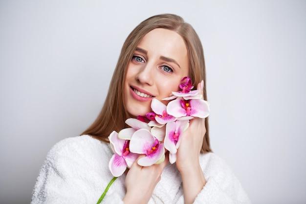 Soins du visage. jeune femme avec une belle peau tient une orchidée.