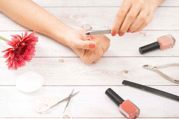 Soins des mains de la femme. gros plan de belles mains féminines ayant une manucure spa au salon de beauté. esthéticienne classant les clients des ongles naturels sains avec une lime à ongles. traitement des ongles. haute résolution