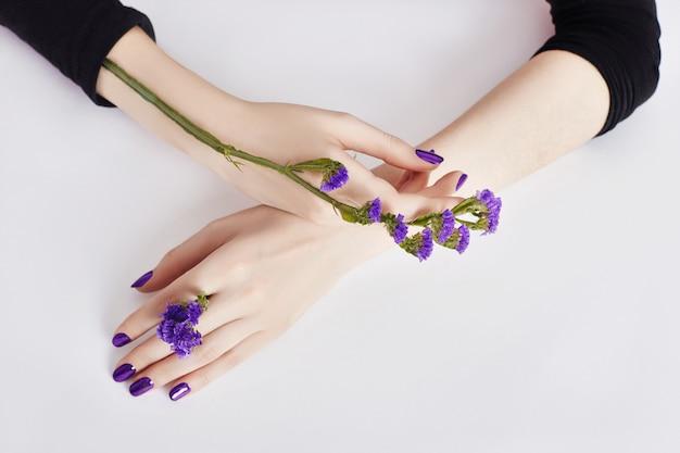 Soins des mains et des fleurs violettes