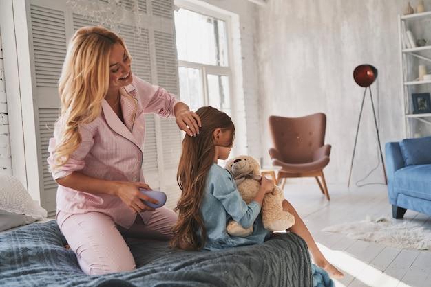 Soins maternels. belle jeune mère se brosse les cheveux de sa fille assise sur le lit à la maison