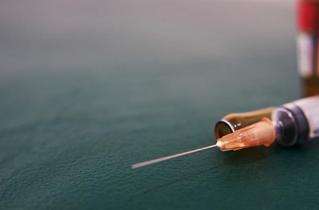 Soins médicaux en seringue et ampoule de médicament cassés à l'hôpital de traitement sur le sol vert