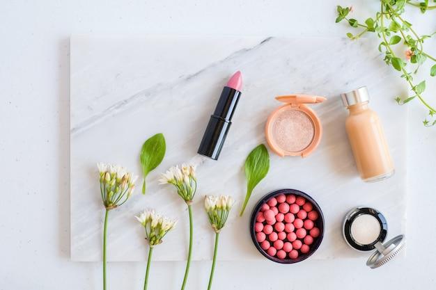 Soins naturels sur table en marbre avec mortier de fleurs, de feuilles et de pilon. concept de beauté cosmétique.