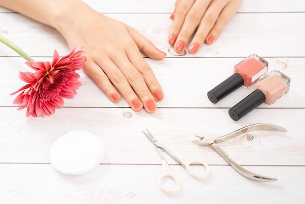 Soins des ongles et manucure. belles mains féminines avec du vernis à ongles rose