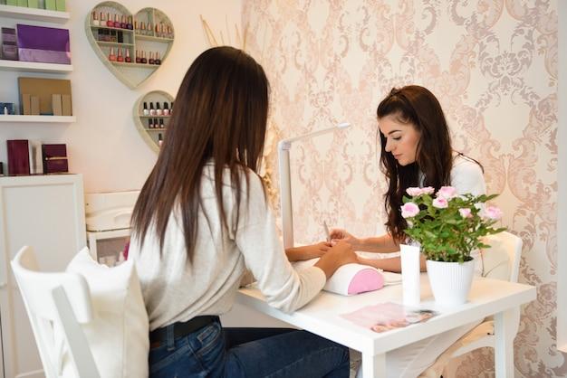 Soins des ongles manucure pour le client assis à une table dans le bureau.
