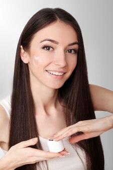 Soins de la peau de beauté. belle femme appliquant une crème cosmétique pour le visage
