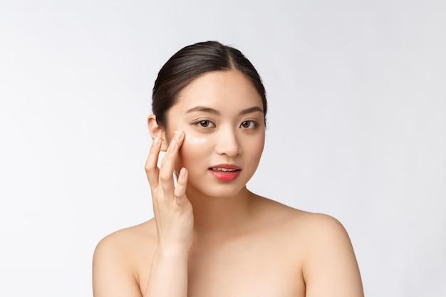 Soins de la peau beauté femme beauté femme souriante appliquant la crème beauté portrait de beau modèle féminin asiatique caucasien isolé sur