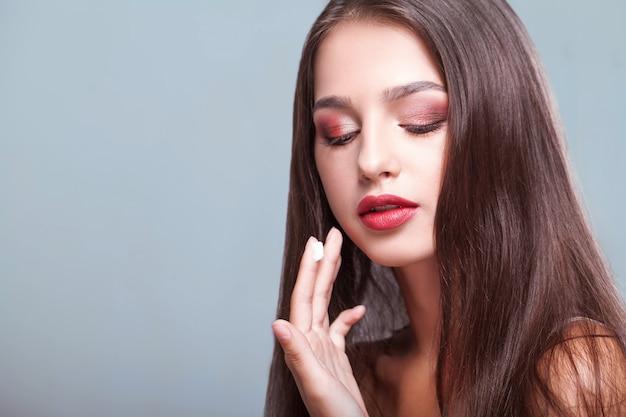 Soins de la peau de beauté. jeune femme, à, maquillage naturel, appliquer, crème
