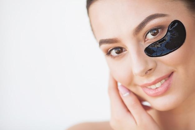 Soins de la peau. belle fille avec des patchs noirs cosmétiques sous les yeux, une peau parfaite et un maquillage naturel.
