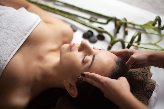 Soins de la peau et du corps. gros plan, jeune, femme, obtenir, traitement spa, à, salon beauté massage du visage au spa. traitement de beauté du visage. salon spa.