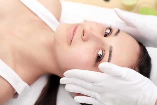 Soins de la peau et du corps. gros plan d'une jeune femme recevant un traitement de spa au salon de beauté. massage du visage au spa. traitement de beauté du visage. salon de spa.