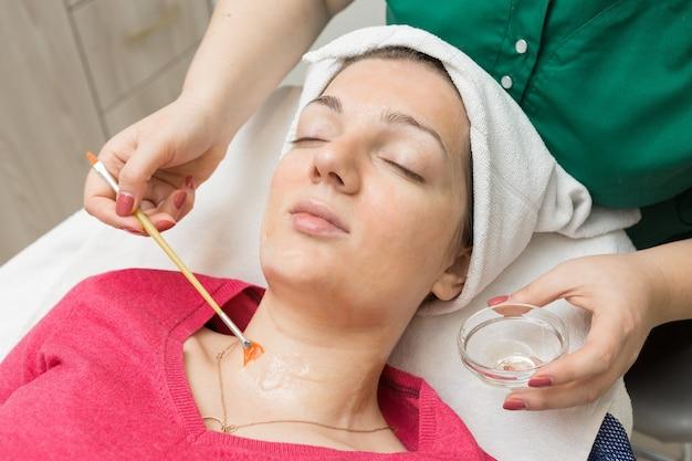 Soins de la peau du visage. esthéticienne appliquant un masque à l'huile de beauté sur le visage à l'aide d'une brosse dans un salon de spa