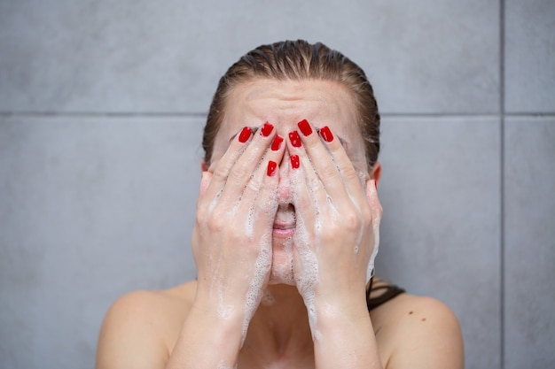 Soins de la peau du visage. femme appliquant un nettoyant pour le visage sur le visage agrandi. fille utilisant un produit cosmétique nettoyant sur la peau, se lavant le visage sur fond clair