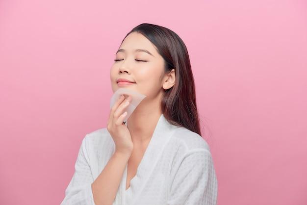 Soins de la peau du visage. femme souriante utilisant un portrait de papier buvard à l'huile pour le visage.