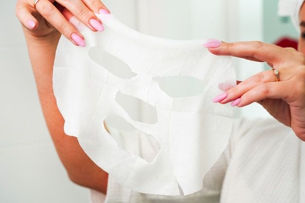 Soins de la peau du visage hydratant concept de cosmétiques coréens portrait de belle femme enlevant le shee blanc...