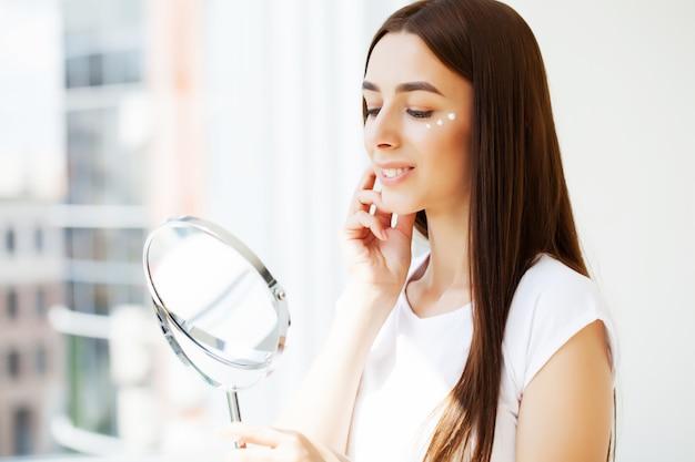 Soins de la peau du visage, jeune femme applique une crème pour le visage dans la salle de bain spacieuse d'un hôtel de luxe