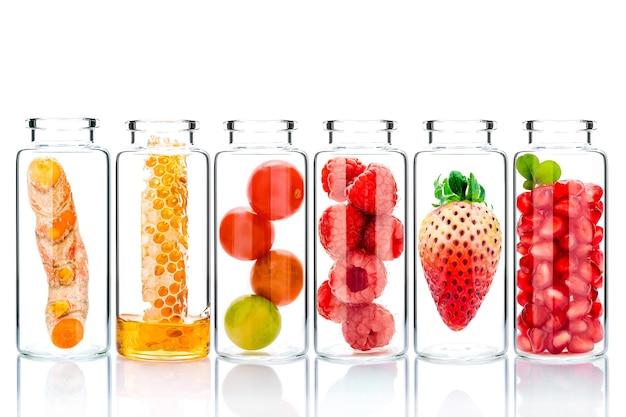 Soins de la peau faits maison avec des ingrédients naturels et des herbes dans des bouteilles en verre isoler sur blanc.