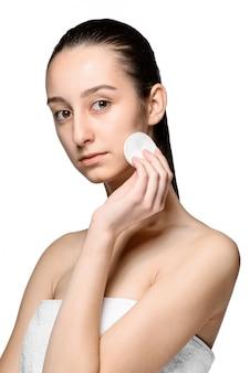 Soins de la peau femme enlevant le visage avec un coton-tige