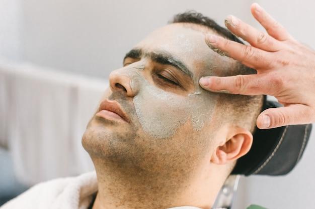 Soins de la peau masculine dans un salon de beauté. appliquer un masque nettoyant à l'argile sur le visage d'un homme